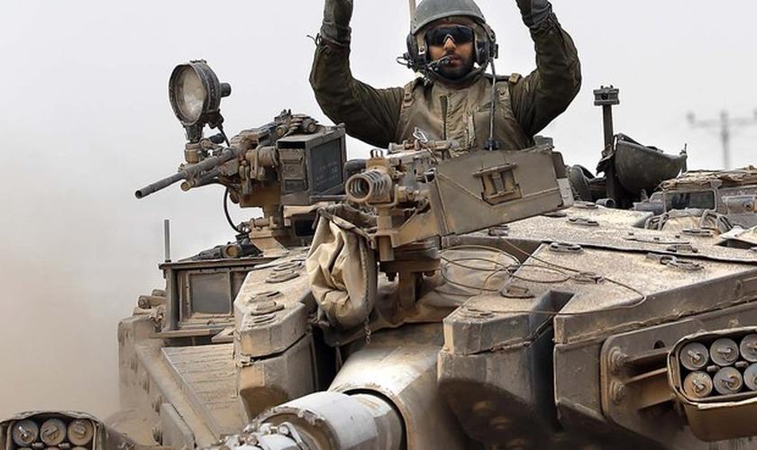 Um soldado israelense faz sinal de vitória a bordo de seu tanque perto da fronteira entre Israel e a Faixa de Gaza
