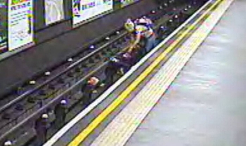 Momento em que a mãe resgata o bebê que caiu nos trilhos do trem, dentro do carrinho