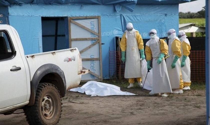 Agentes da saúde se preparam para trabalhar do lado de fora de uma unidade de isolamento na Libéria