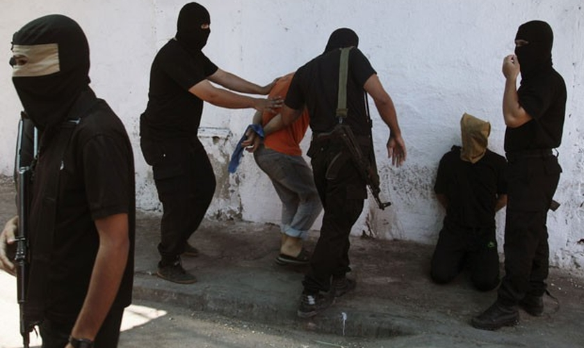 Militantes do Hamas cercam palestinos acusados de terem colaborado com Israel nesta sexta-feira(22); 18 foram mortos