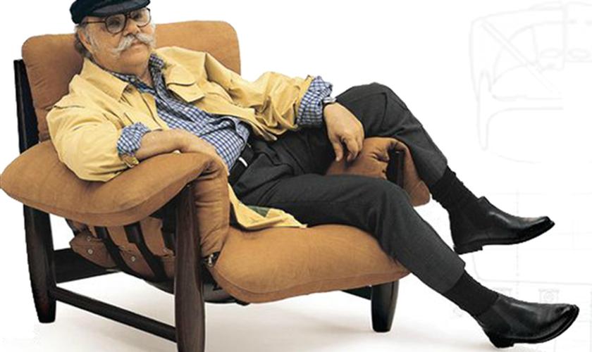 O designer Sergio Rodrigues em uma de suas mais famosas criações, a poltrona Mole, de 1961