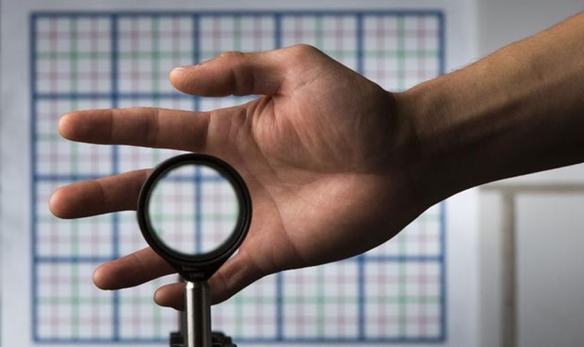 A imagem mostra a mão do estudante Joseph Choi demonstrando o funcionamento das lentes que deixam qualquer coisa invisível
