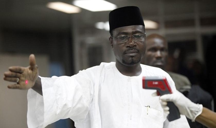 Oficial usa termômetro em passageiro na entrada do aeroporto Murtala Muhammed em Lagos, na Nigéria, em foto de 6 de agosto