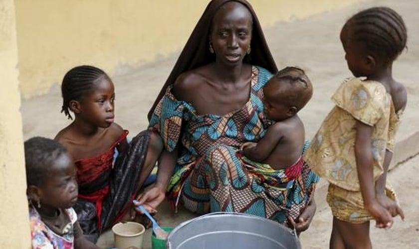 Mulher resgatada dos domínios do Boko Haram pelo exército nigeriano alimenta seus filhos em acampamento para refugiados
