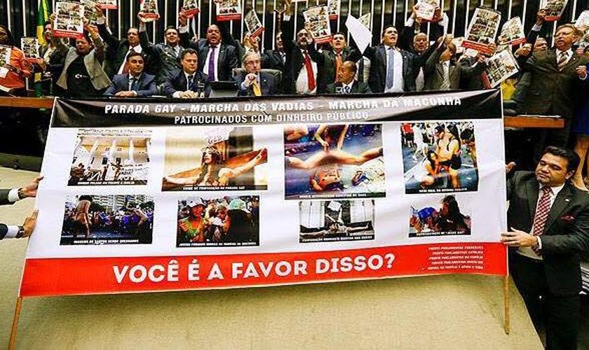 Deputados Evangélicos e católicos expõem cartazes com imagens de protestos que ofenderam o cristianismo, com a profanação de ícones religiosos.