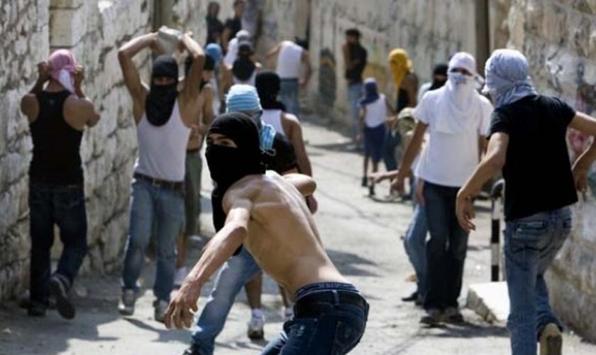 Jovens palestinos atiram pedras contra forças israelenses em Jerusalém (Foto: AFP)