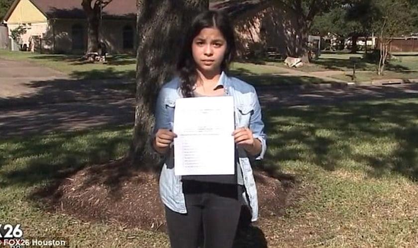 """A estudante Jordan Wooley exibe a folha com a atividade polêmica, que exigia que ela afirmasse que """"Deus é um mito"""". (Imagem: Fox 26)"""