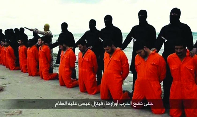 Militantes do Estado Islâmico se posicionam atrás de 21 cristãos coptas, momentos antes de registrarem a execução destes, que barbarizou o mundo em fevereiro de 2014 (Imagem: Reprodução)