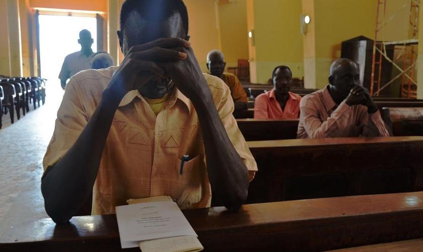 Cristão sudanês ora dentro do templo de igreja. (Foto: La Stampa)
