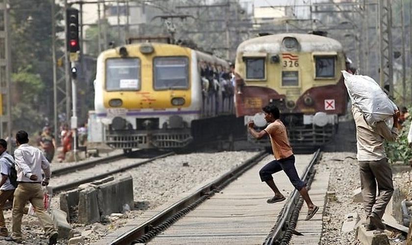 Imagem ilustrativa. Jovem atravessa trilho diante de um trem em funcionamento, em Mumbai, na Índia. (Foto: Reprodução)
