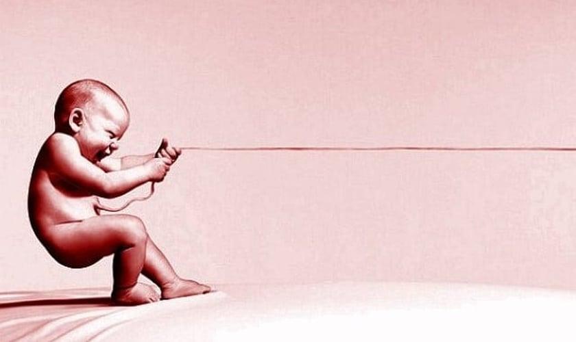 Bebê puxando cordão umbilical. (Imagem: Pensador Anônimo)