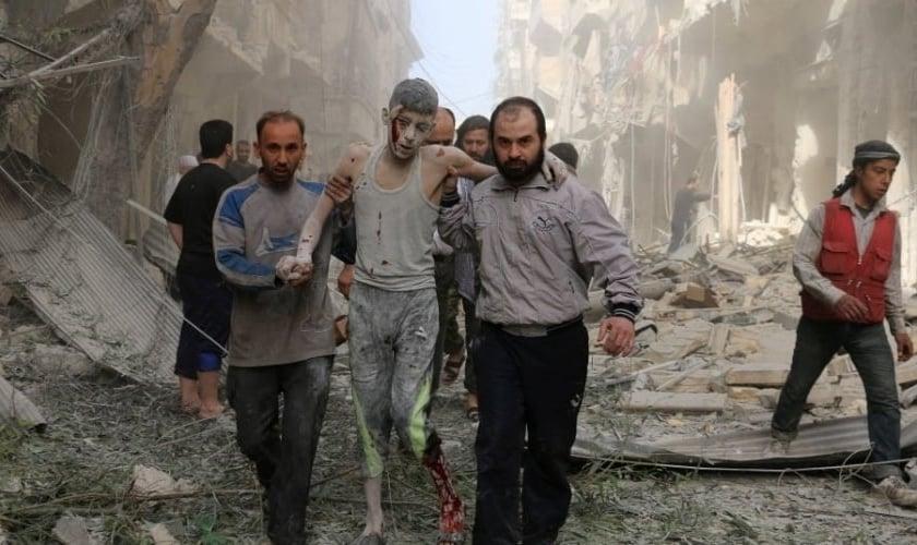 Sírios ajudam um jovem ferido após um ataque aéreo em Aleppo. (Foto: Ameer Alhalbi/AFP)