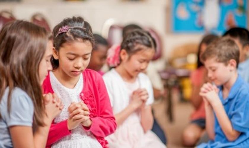 Crianças participam de momento de oração em escola. (Foto: Cedar Brook School)