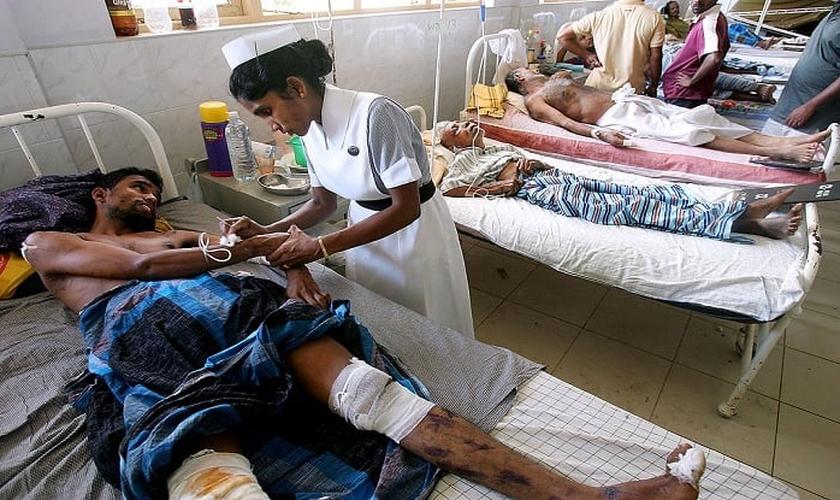 Imagem ilustrativa. Enfermeira cuida de homem enfermo em hospital, na Índia. (Foto: Reprodução)