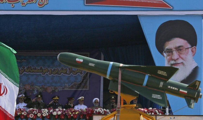 Caminhão militar transportando mísseis diante do retrato do líder supremo do Irã, aiatolá Ali Khamenei. (Foto: Getty Images)