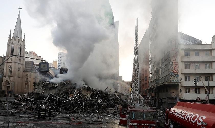 O templo histórico da Igreja Evangélica Luterana (à esquerda) foi seriamente danificado pelos escombros do edifício invadido que desabou no Centro de São Paulo. (Foto: G1)