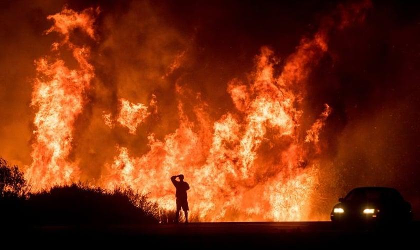 Motorista assiste as chamas do incêndio Thomas ao norte de Ventura, na Califórnia. (Foto: AP/Noah Berger)