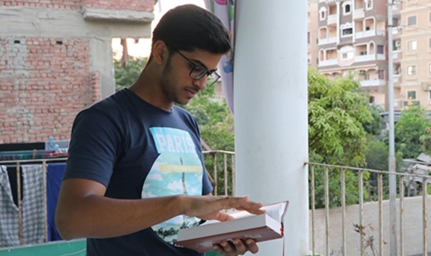 Marcos lê a Bíblia de seu pai, que ainda guarda como lembrança, após o assassinato, no Egito. (Foto: Portas Abertas/EUA)