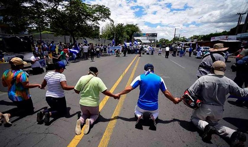 Em manifestação, os cristãos resolveram se ajoelhar e clamar a Deus para que se normalize a situação do país. (Foto: CBN News).