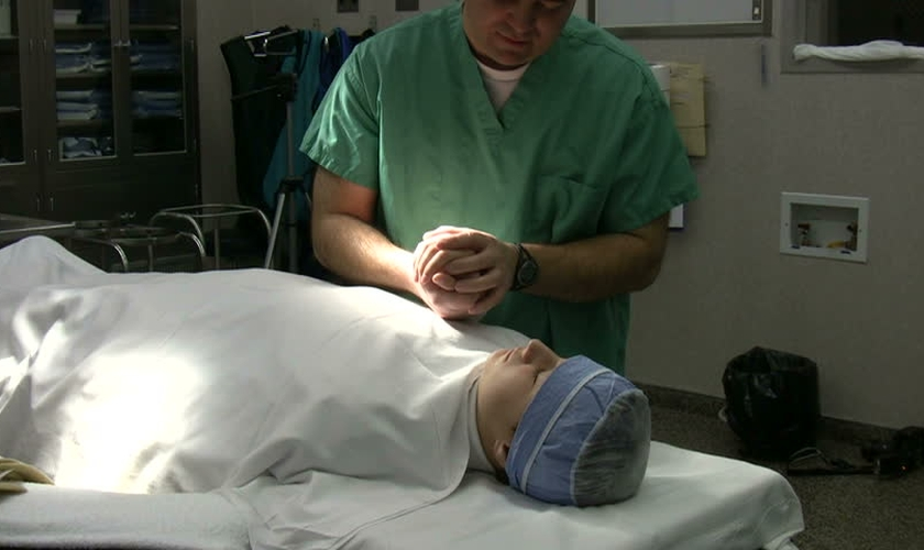 Imagem ilustrativa. Médico em oração com paciente antes de cirurgia. (Foto: John Neff/Shutterstock)