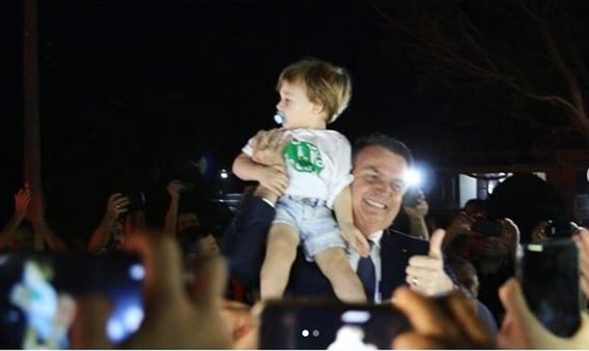 Bolsonaro segura nos braços o pequeno Noach, neto do pastor Joel Engel. (Foto: Arquivo pessoal)