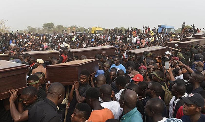 Homens carregam caixões em velório coletivo, após massacre na Nigéria. (Foto: Independent)