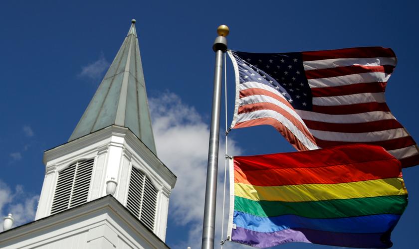 Bandeira do orgulho gay junto com a bandeira dos EUA em frente à Igreja Metodista Unida de Asbury, nos EUA. (Foto: AP)