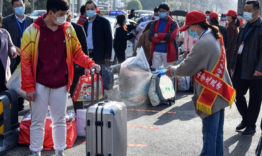 Voluntária aplica desinfetante sobre a bagagem de um aluno em Bozhou, na província de Anhui, no leste da China. (Foto: AFP)