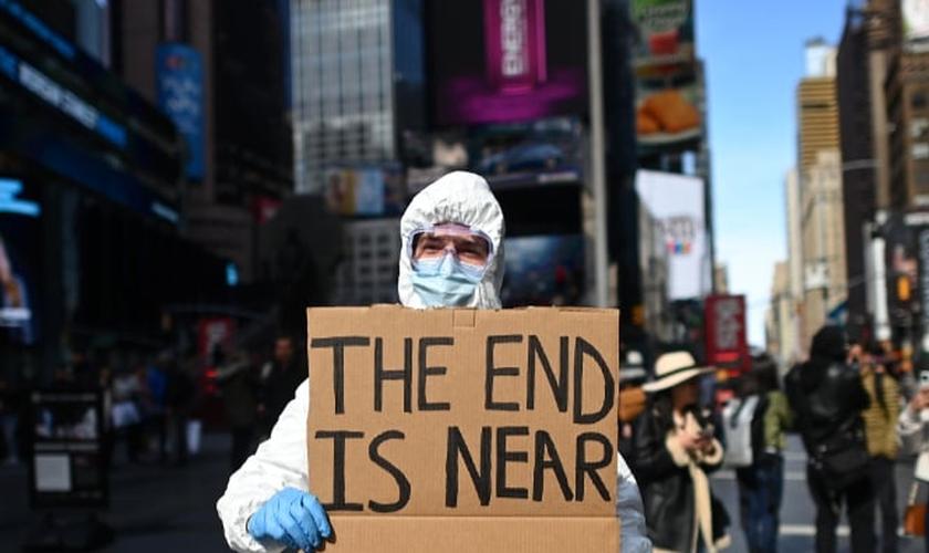 """""""O fim está próximo"""", diz manifestante em cartaz sobre coronavírus na Times Square, em Nova York. (Foto: Johannes Eisele/AFP)"""