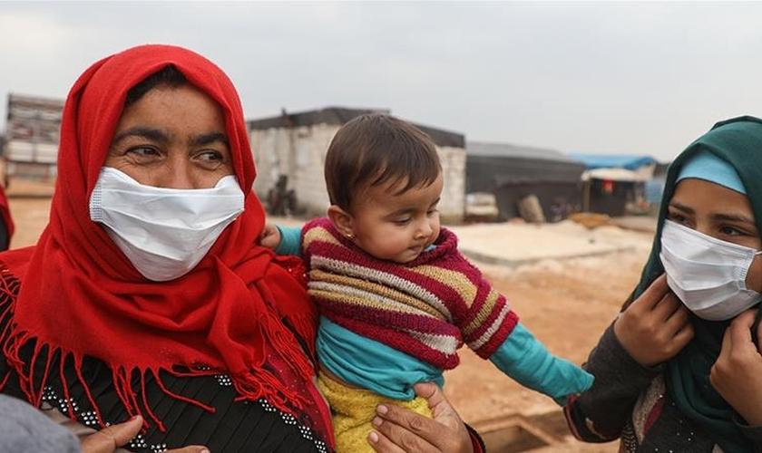 Mulheres usam máscaras em um campo para deslocados na província de Idlib. (Foto: Aaref Watad / AFP)