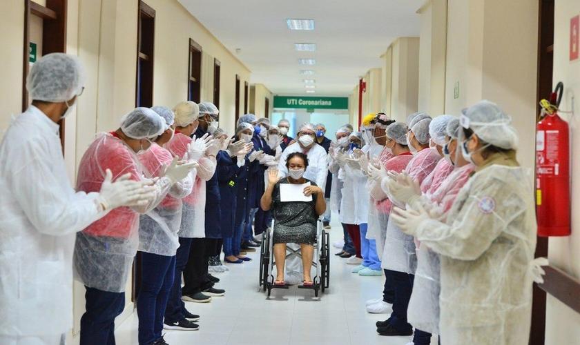 Mulher deixa hospital sendo aplaudida por equipe médica no Amazonas. (Foto: G1)