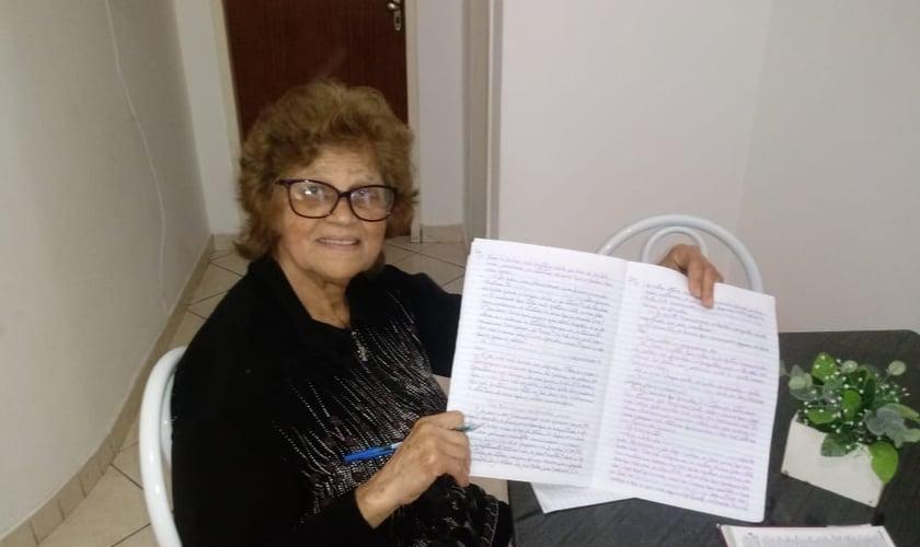 Maria Petrina exibe um dos cadernos com cópias da Bíblia. (Foto: Reprodução)