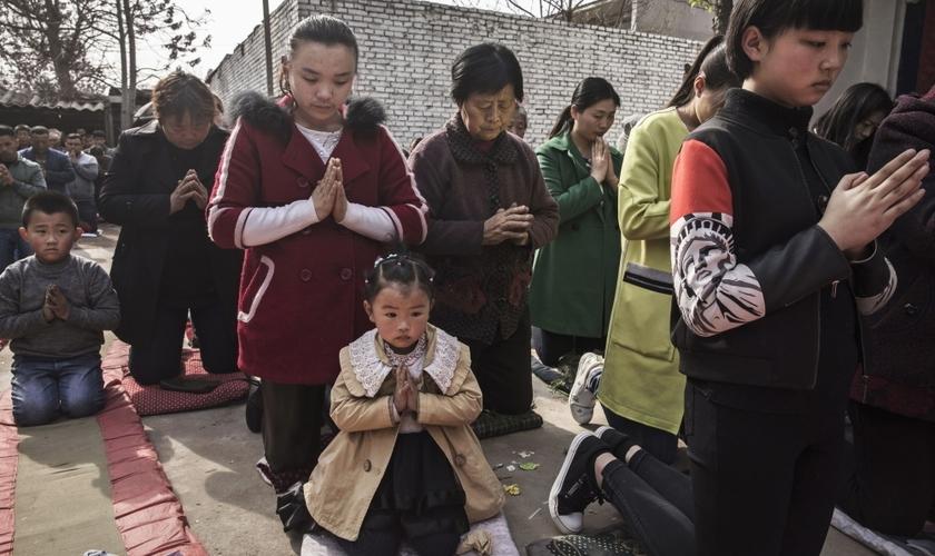 Cristãos chineses oram ajoelhados durante um culto de Páscoa em uma igreja não oficial. (Foto: Getty Images / Kevin Frayer)