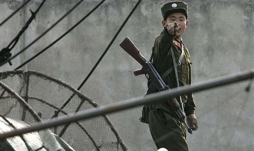 Soldado norte-coreano caminha com fuzil pendurado no ombro. (Foto: Ary News)