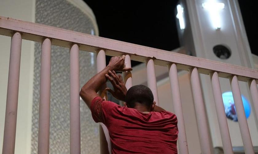 Homem do lado de fora de igreja fechada no Rio de Janeiro. (Foto: Ricardo Moraes/Reuters)