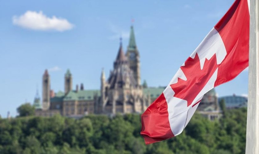 Bandeira canadense, com o parlamento ao fundo. (Foto: Reprodução / Shutterstock)