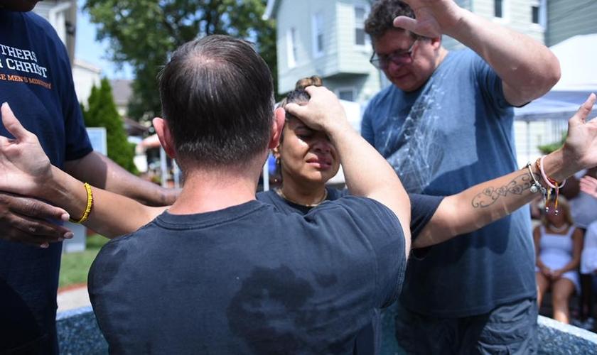 Pastor Steve Hannett ora por mulher durante batismo. (Foto: Abundant Grace Christian Church)