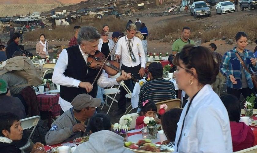 O evangelista Georgian toca violino durante ação social em comunidade pobre. (Foto: Reprodução/Facebook).