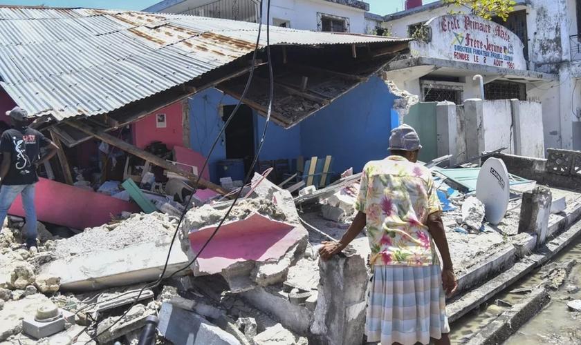 Mulher observa o que sobrou de uma casa que desabou no terremoto deste sábado (14), em Les Cayes, no Haiti. (Foto: Duples Plymouth/AP)