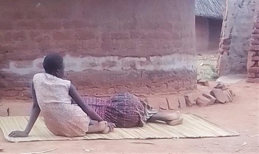 Harriet Nanzala descansa ao lado de sua filha no leste de Uganda. (Foto: Reprodução / Morning Star News)