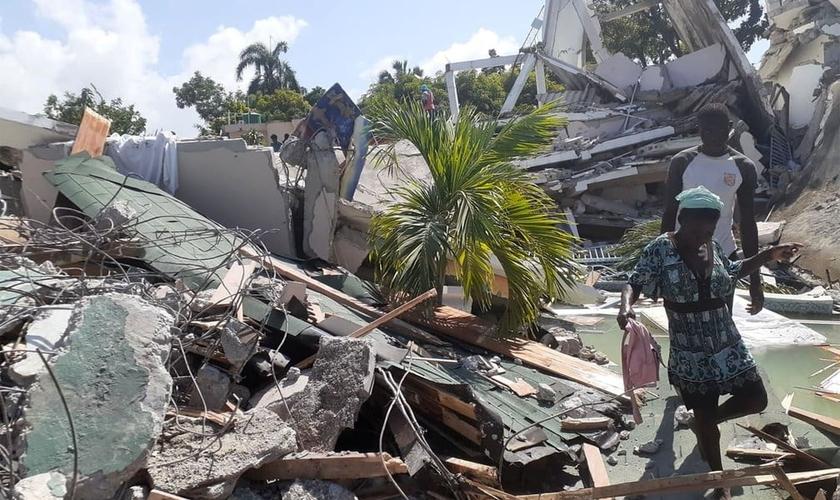 Pessoas caminham entre escombros de casas destruídas pelo terremoto em Les Cayes, no Haiti. (Foto: Jose Flecher/Reuters).