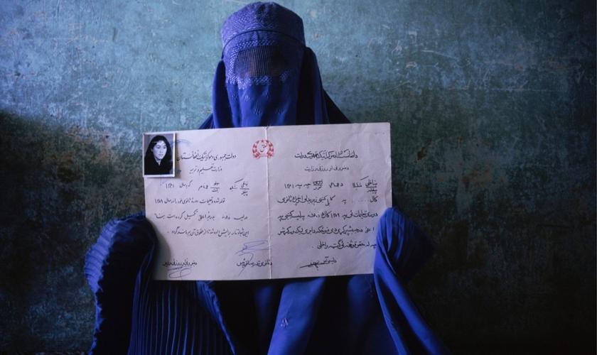 Mulher segura seu diploma de quando estudava, antes da tomada do poder pelo Talibã. (Foto: Nina Berman/NOOR)