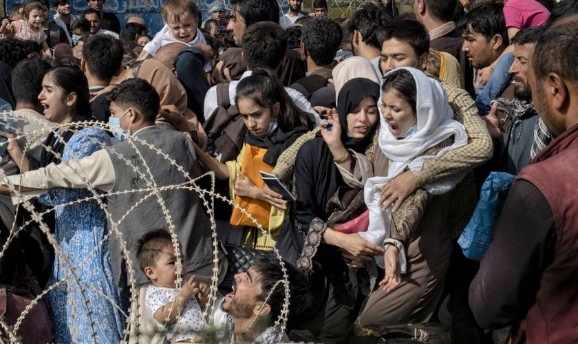 Afegãos se aglomeram junto aos muros do aeroporto de Cabul na esperança de serem retirados do país. (Foto: Juan Carlos/El País)