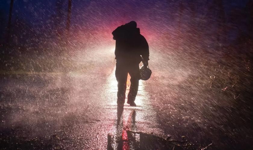 Um chefe de bombeiros voltando para o seu caminhão, na chuva, em Louisiana, depois da passagem do furacão Ida. (Foto: Mark Felix/AFP)
