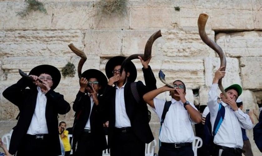 Judeus ultraortodoxos tocam o shofar enquanto os fiéis oram no Muro das Lamentações. (Foto: Reprodução / El País)