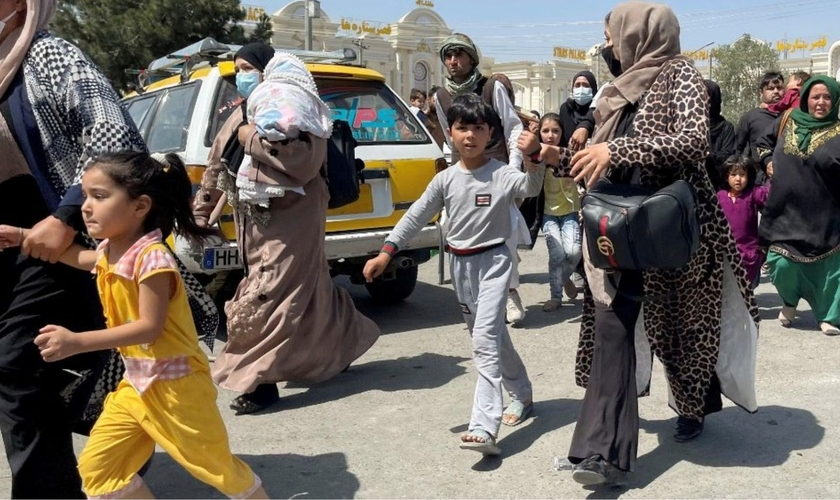 Mães e filhos tentam entrar no aeroporto Hamid Karzai, em Cabul, para fugir do país. (Foto: Reuters)