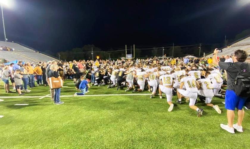 Jogadores de futebol conduzem pais e torcedores em oração após jogo no Condado de Putnam, nos EUA. (Foto: Bob Vick)
