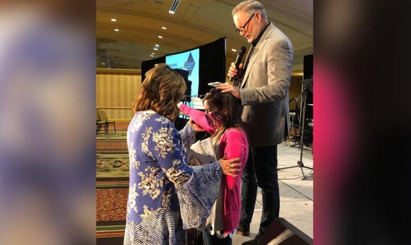 Rita DuBose (à esq.) e seu marido oram por Cassie Fawns durante culto. (Foto: AG News)