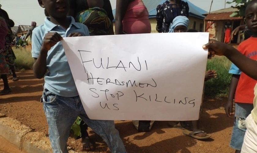Nigerianos seguram uma placa pedindo o fim dos assassinatos. (Foto: Reprodução / ECCVN)
