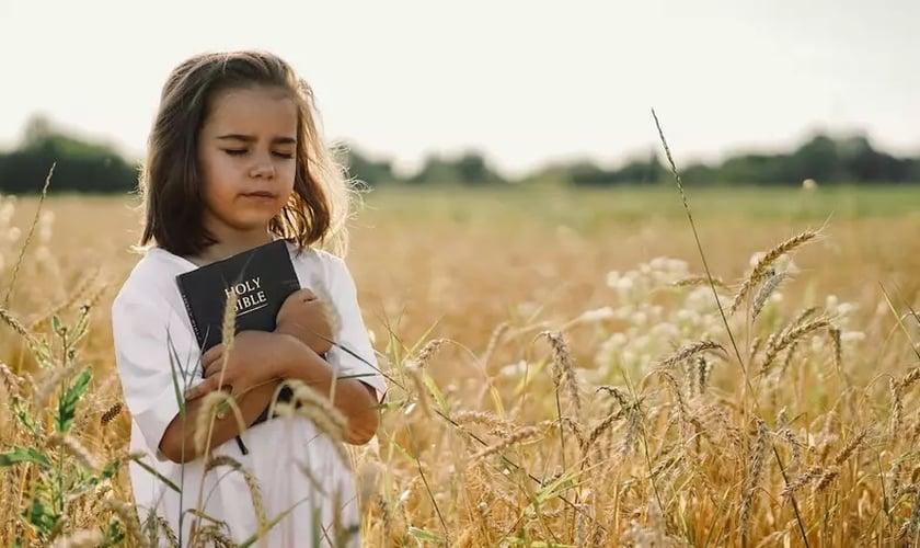 Menina segura sua Bíblia. (Foto: Getty Images / Anastasiia Stiahailo)
